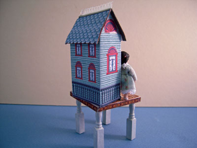 "Loretta Kasza 1"" scale hand crafted blue dollhouse on a table"