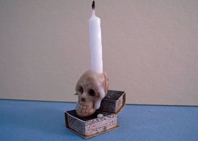 """1"""" scale skull candle on books"""